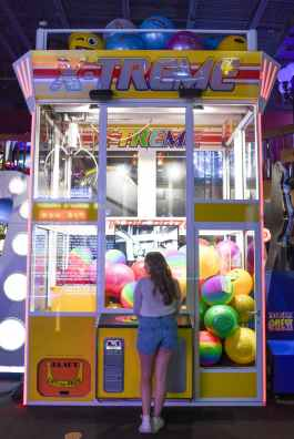 woman standing in front of x treme arcade machine